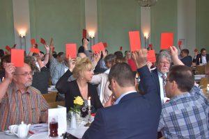 Delegierte des SPD-Bezirksparteitags heben Stimmzettel