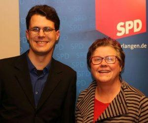 Philipp Dees und Gisela Niclas vor einem Banner der SPD Erlangen