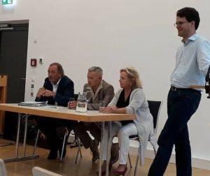 Franz Schindler, Horst Arnold und Alexandra Hiersemann während der Diskussion am Tisch sitzend, daneben steht Dr. Philipp Dees
